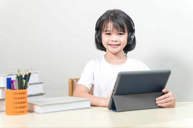 Fröhliche asiatische kleine studentin trägt kopfhörer schreibt auf digitalem tablet, um zu hause zu lernen