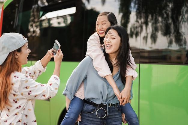 Fröhliche asiatische leute, die spaß mit dem handy am busbahnhof haben - konzentrieren sie sich auf das linke mädchengesicht