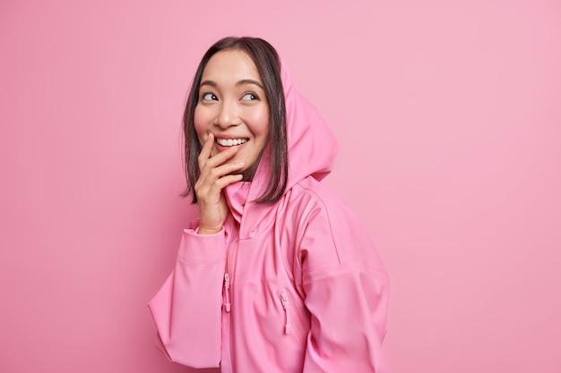 Fröhliche asiatische teenagerin blickt tagträume beiseite und erinnert sich an einen schönen moment, in dem das lächeln breit im hoodie gekleidet ist und positive, ehrliche emotionen ausdrückt, die über einer rosa wand isoliert sind. jugendlebensstil
