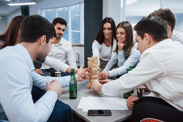 Fröhliche atmosphäre. erfolgreiches geschäft feiern. junge büroangestellte sitzen in der nähe des tisches mit alkohol