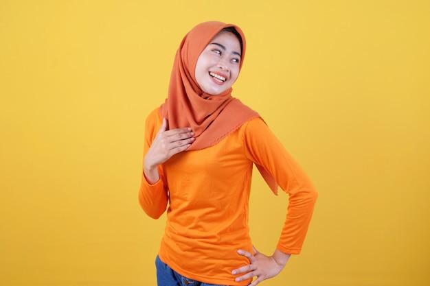 Fröhliche attraktive asiatische frau demonstriert kopierraum auf leerer gelber wand, hat einen fröhlichen freundlichen ausdruck, lässig gekleidet mit hijab, posiert drinnen