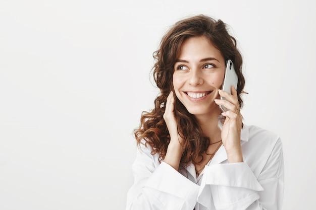 Fröhliche attraktive frau, die am telefon spricht und lächelt