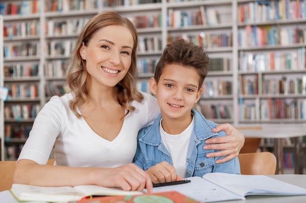 Fröhliche attraktive frau und ihr charmanter kleiner sohn lächelnd, in der bibliothek studierend
