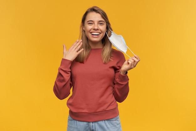 Fröhliche attraktive junge frau, die ihre virusschutzmaske auf gesicht gegen coronavirus abnimmt und über gelbe wand lächelt