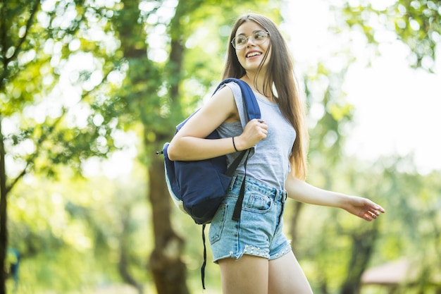 Fröhliche attraktive junge frau mit rucksack und notizbüchern, die im park stehen und lächeln