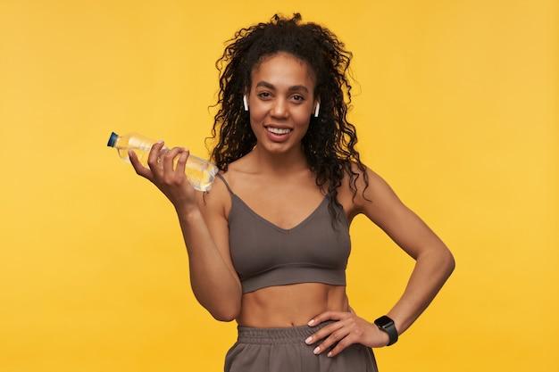 Fröhliche attraktive junge sportlerin mit drahtlosen kopfhörern und intelligenter uhr, die isoliert über gelber wand steht und eine flasche wasser hält