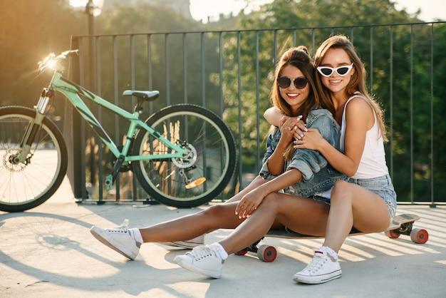 Fröhliche attraktive mädchen in sonnenbrille und stilvollen trendigen kleidern sitzen auf dem skateboard und umarmen sich auf dem hintergrund des stadtbildes.