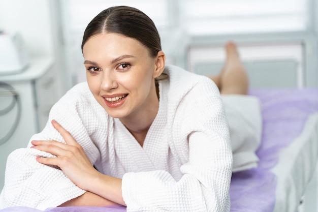 Fröhliche attraktive patientin liegt auf dem bauch auf einer couch in einer schönheitsklinik