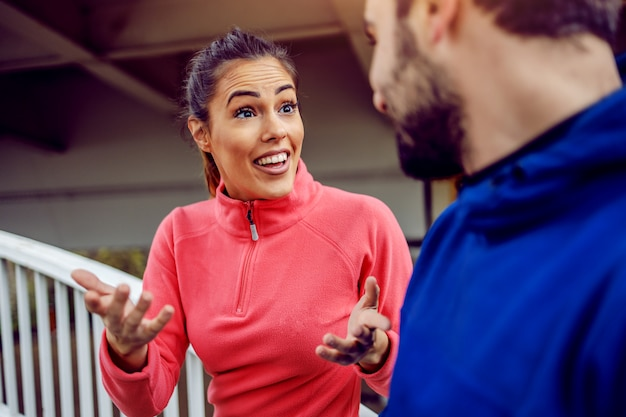 Fröhliche, attraktive sportlerin, die mit ihrem männlichen freund die brücke besteigt und über die vorteile des laufens spricht. konzept des städtischen lebens.