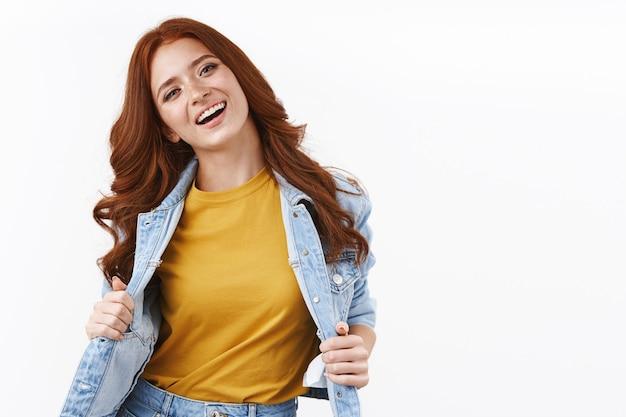 Fröhliche attraktive, stylische rothaarige in jeansjacke, gelbes t-shirt, geneigter kopf und zufriedenes lächeln, sorglos und fröhlich, weiße wand