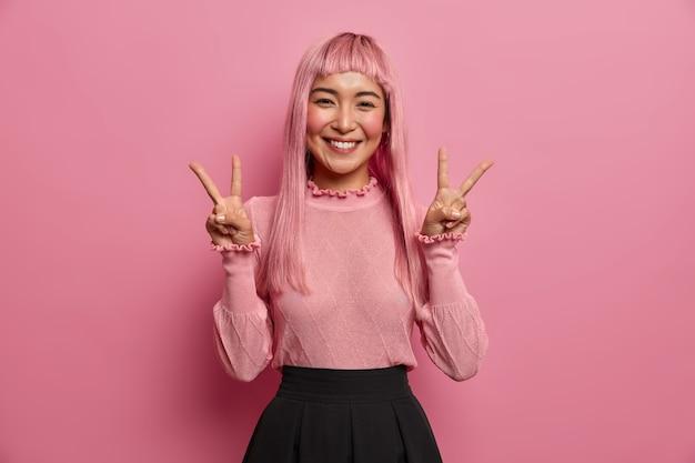 Fröhliche aufgeregte junge asiatische frau mit langen rosa haaren gibt siegeszeichen, zeigt zwei finger, lächelt positiv