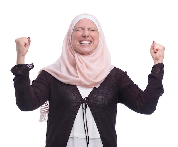 Fröhliche aufgeregte muslimische frau, die erfolg über weiße wand feiert