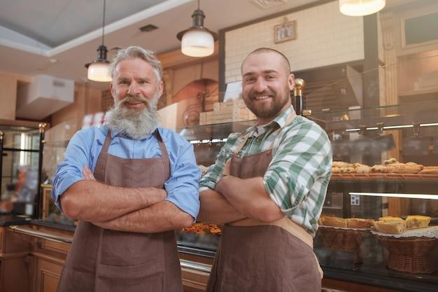 Fröhliche bäcker von vater und sohn, die gerne in ihrer bäckerei arbeiten