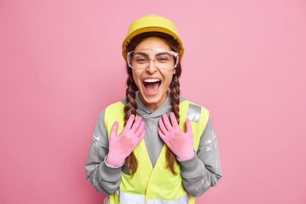Fröhliche baufrau bereitet sich auf den wiederaufbau vor gebäude inspiziert baustelle trägt schutzbrille huthandschuhe lacht positiv zufrieden mit arbeitsergebnissen. aufrechterhaltung des arbeitsplatzes.