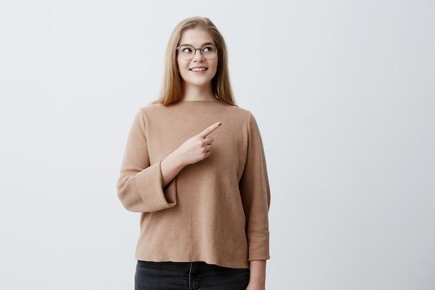 Fröhliche blonde europäische weibliche punkte mit dem vorderfinger beiseite auf dem kopierraum, hat weiße perfekte zähne und ein breites lächeln. charmantes mädchen lässig gekleidet bewirbt etwas an der leeren wand