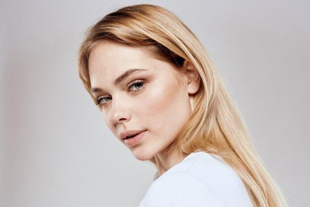 Fröhliche blonde frau im weißen t-shirt lokalisiert