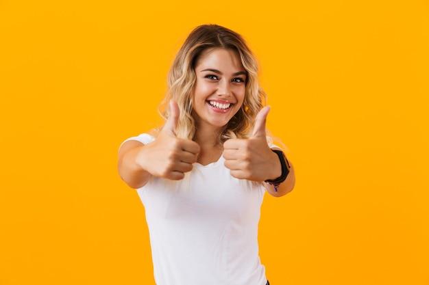 Fröhliche blonde frau in der grundkleidung, die lächelt und daumen hoch zeigt, lokalisiert über gelber wand