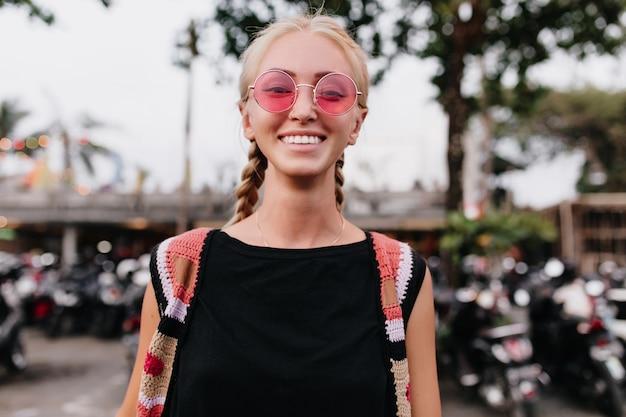 Fröhliche blonde frau in strickkleidung, die zeit im freien verbringt. frau mit blonden zöpfen, die rosa sonnenbrille tragen.