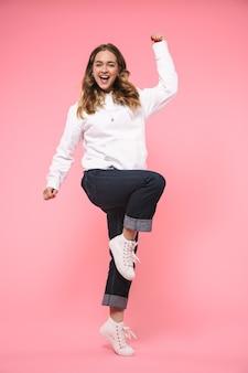 Fröhliche blonde frau in voller länge, die in freizeitkleidung trägt, freut sich und schaut auf die vorderseite über rosa wand