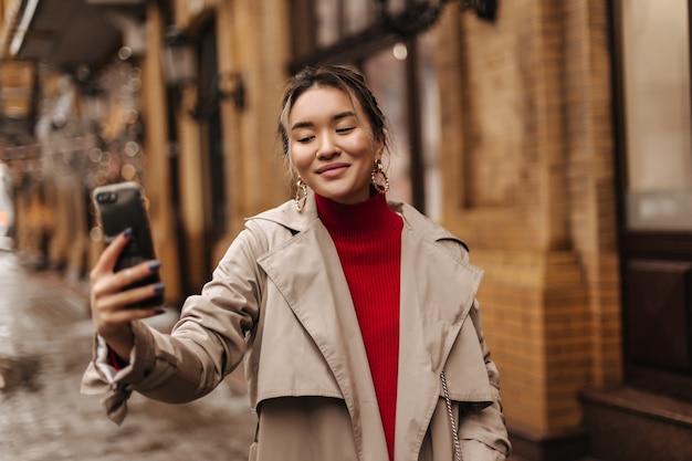 Fröhliche blonde frau macht selfie, das in der europäischen stadt geht