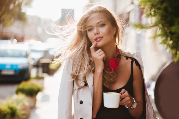 Fröhliche blonde frau mit inspiriertem lächeln, das mit tasse kaffee am sonnigen tag aufwirft. außenporträt des niedlichen weiblichen modells, das ihre lippe mit finger berührt und latte in der hand hält.