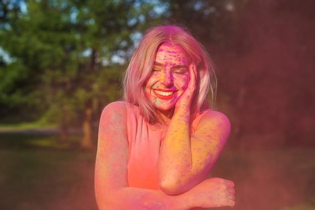 Fröhliche blonde frau mit langen haaren bedeckte lila trockene farbe, die das holi-festival feierte
