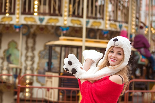 Fröhliche blonde frau mit rotem strickpullover und lustigem hut, die im hintergrund des karussells mit lichtern posiert