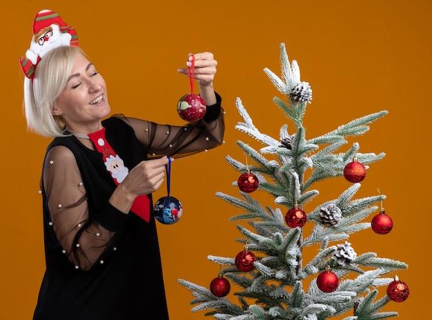 Fröhliche blonde frau mittleren alters mit weihnachtsmann-stirnband und krawatte, die in der profilansicht in der nähe des geschmückten weihnachtsbaums steht und weihnachtskugeln hält, die mit geschlossenen augen isoliert auf oranger wand lachen