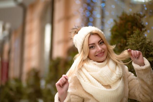 Fröhliche blonde frau trägt weiße strickmütze und schal, posiert auf dem hintergrund von bokeh