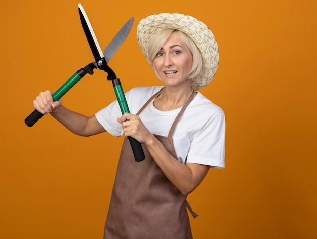 Fröhliche blonde gärtnerin mittleren alters in uniform mit hut, die eine heckenschere isoliert auf oranger wand mit kopierraum hält