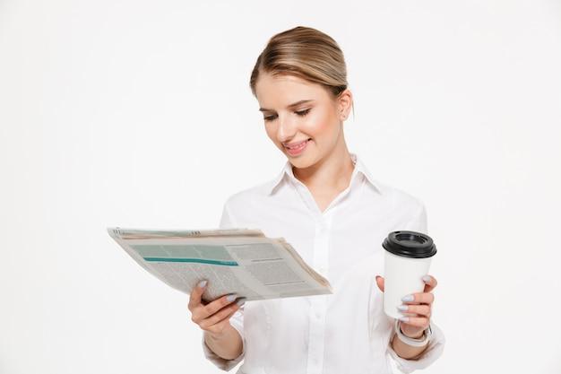 Fröhliche blonde geschäftsfrau, die zeitung liest, während tasse kaffee über weißer wand hält