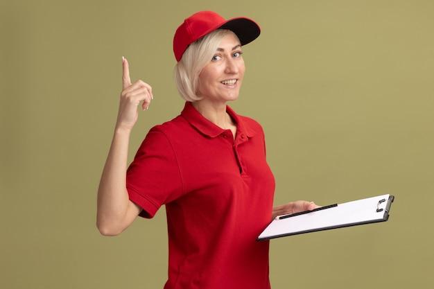 Fröhliche blonde lieferfrau mittleren alters in roter uniform und mütze, die in der profilansicht steht und klemmbrett und bleistift nach oben hält