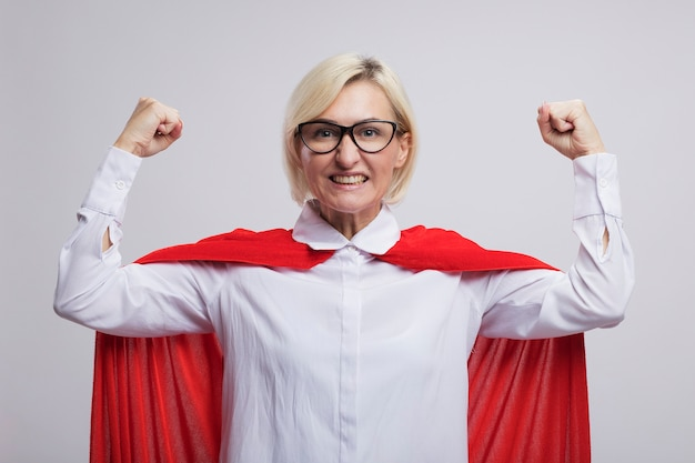 Fröhliche blonde superheldin mittleren alters im roten umhang mit brille, die eine starke geste macht