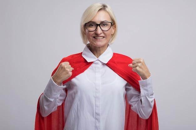 Fröhliche blonde superheldin mittleren alters im roten umhang mit brille, die ja-geste macht