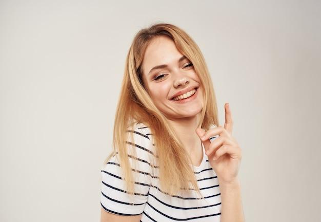 Fröhliche blondine auf einem licht zeigt einen finger und ein kurzes gestreiftes t-shirt ist zu sehen