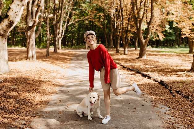 Fröhliche blondine in stilvollem rotem pullover und beigen shorts, die spaß im schönen herbstpark mit ihrem hund haben.