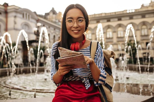 Fröhliche brünette asiatin in brille, gestreiftem hemd und rotem rock lächelt, hält karte und sitzt in der nähe des brunnens