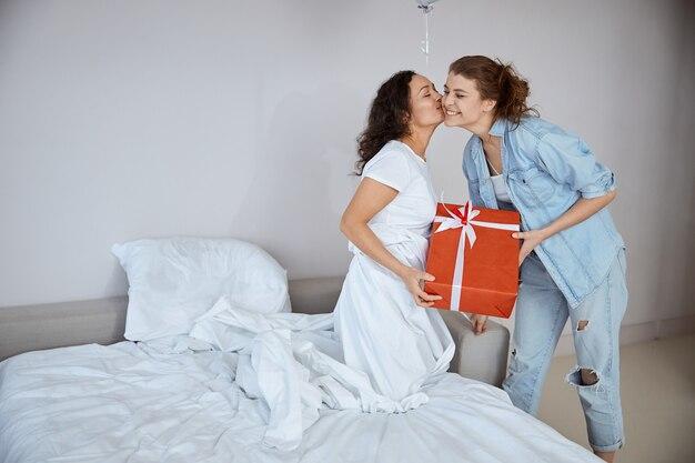 Fröhliche brünette, die ihren partner küsst, während sie ab morgen festliche stimmung hat