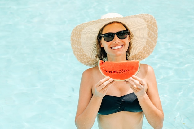 Fröhliche brünette frau in einem schwarzen bikini, der eine wassermelone in ihren händen hält und lächelt
