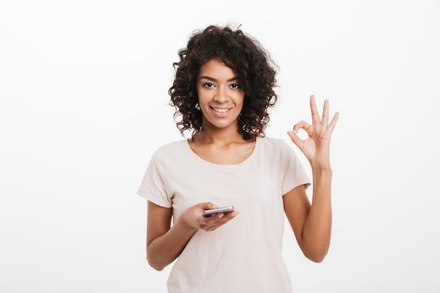 Fröhliche brünette frau mit afro-frisur, die t-shirt unter verwendung des smartphones trägt und ok symbol zeigt, lokalisiert über weißer wand