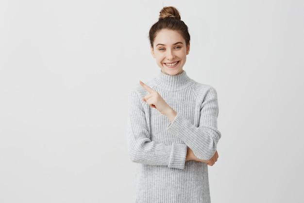 Fröhliche brünette frau posiert und gestikuliert. weiblicher stammkunde, der schönes produkt mit zeigefinger präsentiert. auswahlkonzept