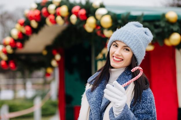Fröhliche brünette frau trägt strickmütze und wintermantel mit süßigkeiten in der nähe der straße weihnachtsentscheidung mit kugeln. platz für text