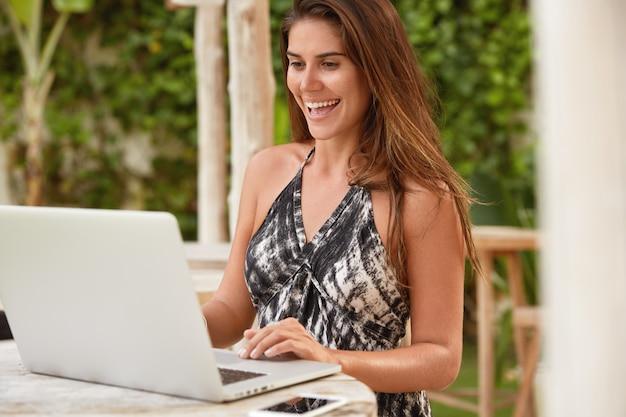 Fröhliche brünette frau überprüft e-mail und nachrichten online auf modernen laptop-computer, hat ein glückliches lächeln, während auf balkon der villa im resort land neu erstellen. menschen, freizeit, lebensstil und emotionen