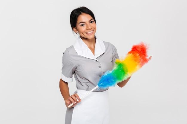 Fröhliche brünette haushälterin in uniform mit buntem staubtuch
