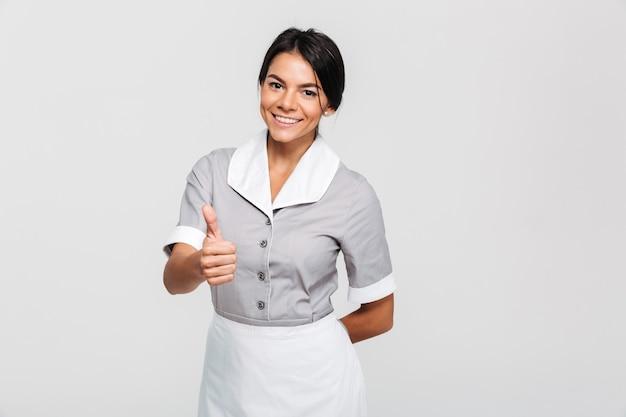 Fröhliche brünette haushälterin in uniform mit daumen hoch geste