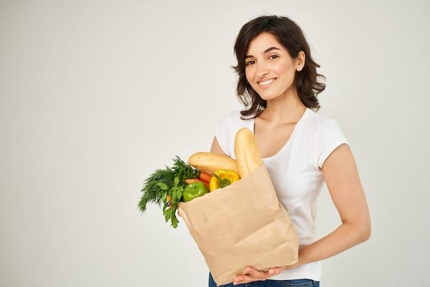 Fröhliche brünette in einem weißen t-shirt-paket mit lebensmittelsupermarktlieferung