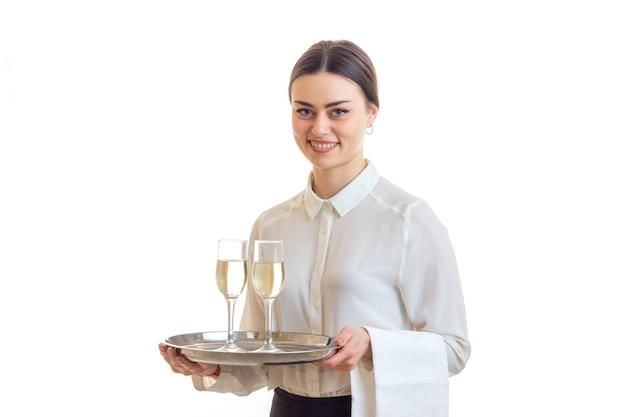 Fröhliche brünette kellnerin lächelt und hält ein trey mit champagner isoliert auf weißem hintergrund