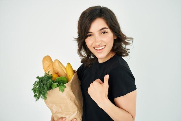 Fröhliche brünette mit einem paket lebensmittel supermarkt für gesunde lebensmittel