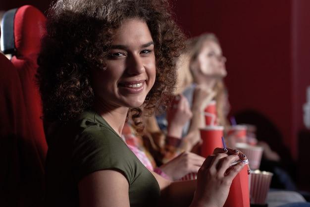 Fröhliche brünette mit schönem lächeln beim essen von popcorn beim ansehen eines interessanten films im kino.
