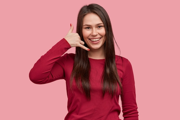 Fröhliche brünette sommersprossige dame macht anrufgeste, hat ein breites lächeln, zeigt weiße zähne, gekleidet in lässigen roten pullover, bittet, sie anzurufen